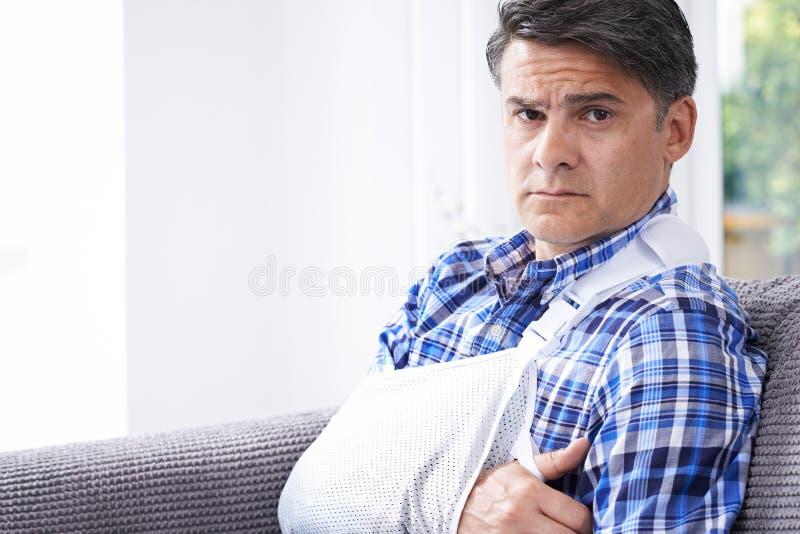 Портрет зрелого человека с рукой в слинге дома стоковое изображение rf
