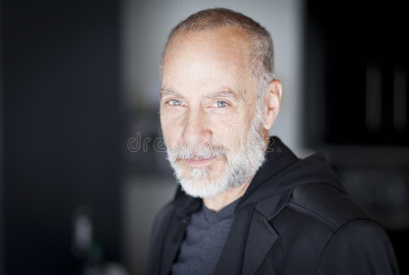 Портрет зрелого человека усмехаясь на камере стоковое фото