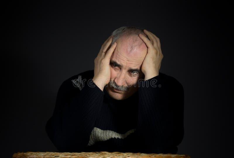 Портрет зрелого человека enfolded его голова с ладонями стоковое изображение rf