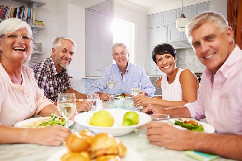 Портрет зрелых друзей наслаждаясь едой дома совместно стоковое изображение