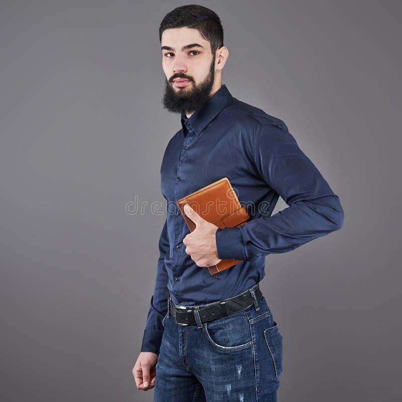 Портрет зубастого красивого бородатого человека с книгой на руках стоковое изображение