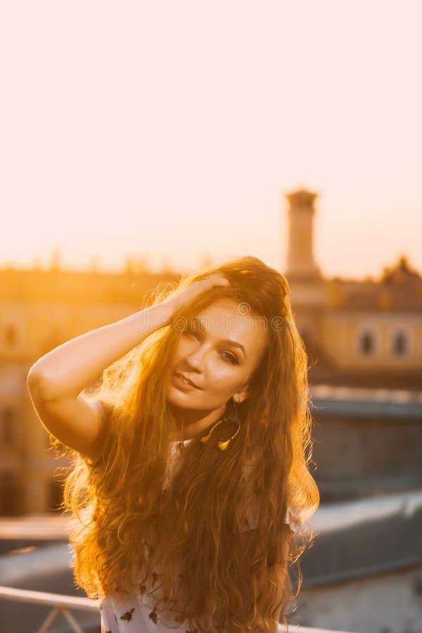 Портрет зубов красивых молодых сексуальных улыбки девушки в белом коротком платье лета на a оранжевого захода солнца стоковые изображения