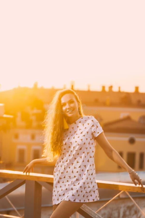 Портрет зубов красивых молодых сексуальных улыбки девушки в белом коротком платье лета на a оранжевого захода солнца стоковое изображение rf