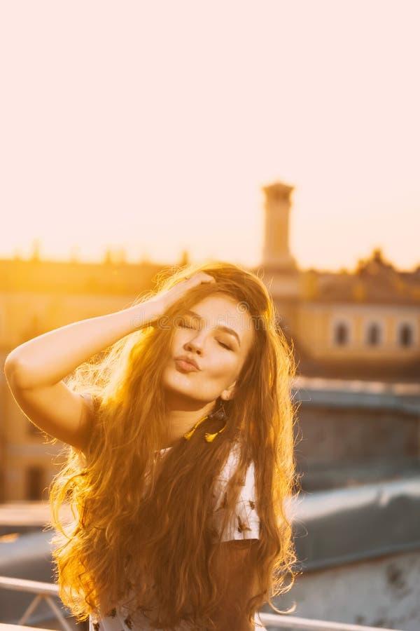 Портрет зубов красивых молодых сексуальных улыбки девушки в белом коротком платье лета на a оранжевого захода солнца стоковое изображение