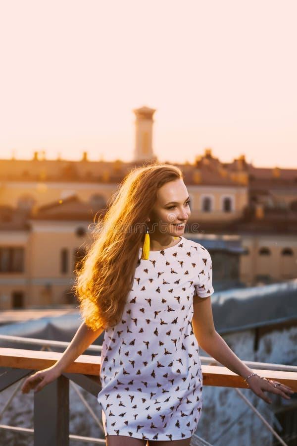 Портрет зубов красивых молодых сексуальных улыбки девушки в белом коротком платье лета на a оранжевого захода солнца стоковая фотография
