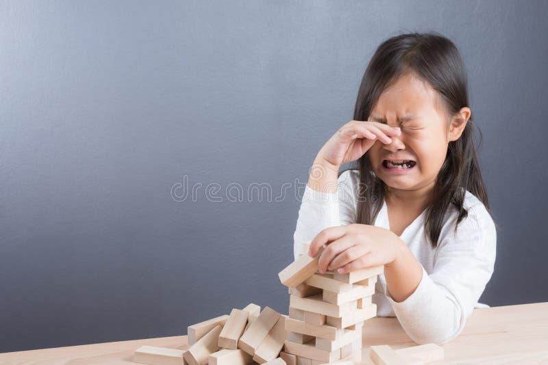 Портрет игры девушки преграждает деревянную игру на backgroun деревянного стола стоковая фотография