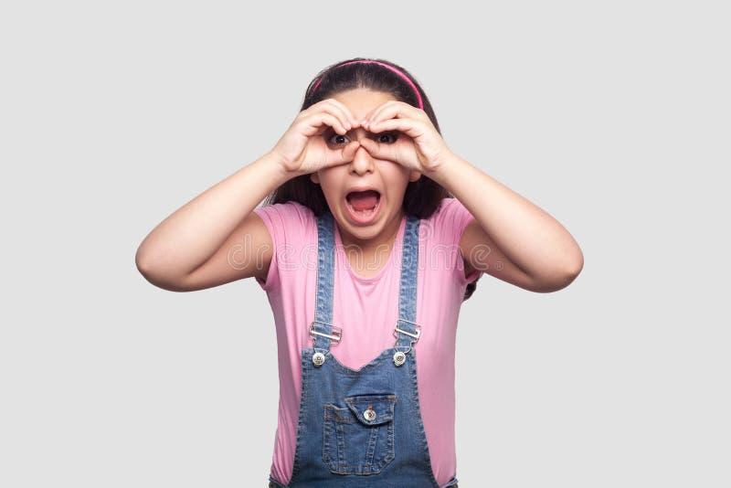 Портрет изумленной маленькой девочки в розовой футболке и голубые прозодежды стоя с биноклями показывают жестами руки на глазах и стоковое фото rf