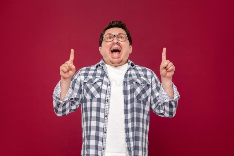 Портрет изумленной смешной середины постарел человек в checkered рубашке, положении eyeglasses, смотря вверх, сотрясенной стороне стоковое фото