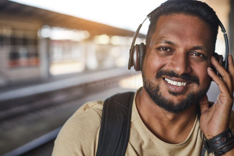 Портрет индусского усмехаясь человека слушая к музыке стоковые изображения
