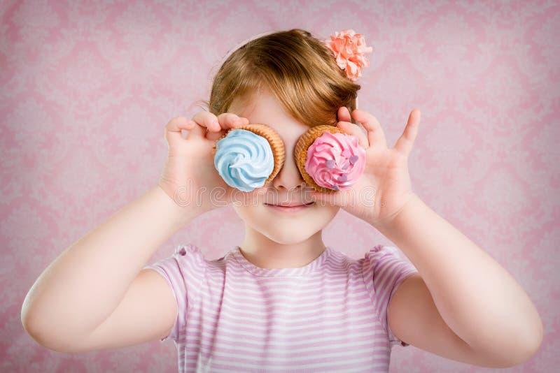 Портрет и пирожные маленькой девочки на розовой предпосылке стоковые фото