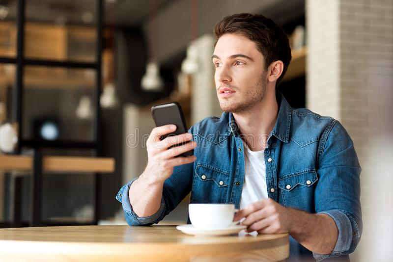 портрет кавказского человека используя цифровой smartphone пока сидящ стоковое фото