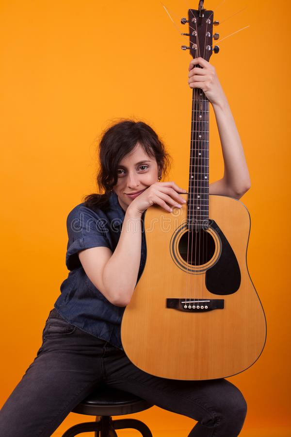 Портрет кавказской женщины с ее acustic гитарой в студии над желтой предпосылкой стоковые фото