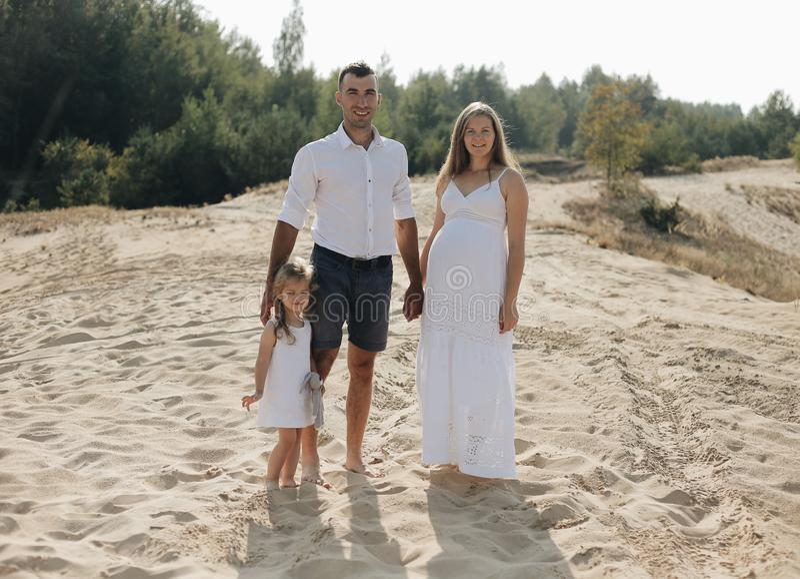 Портрет кавказской семьи с младенцем в белых одеждах стоит на песчанной дюне Беременное mpther Newborn стоковые изображения rf