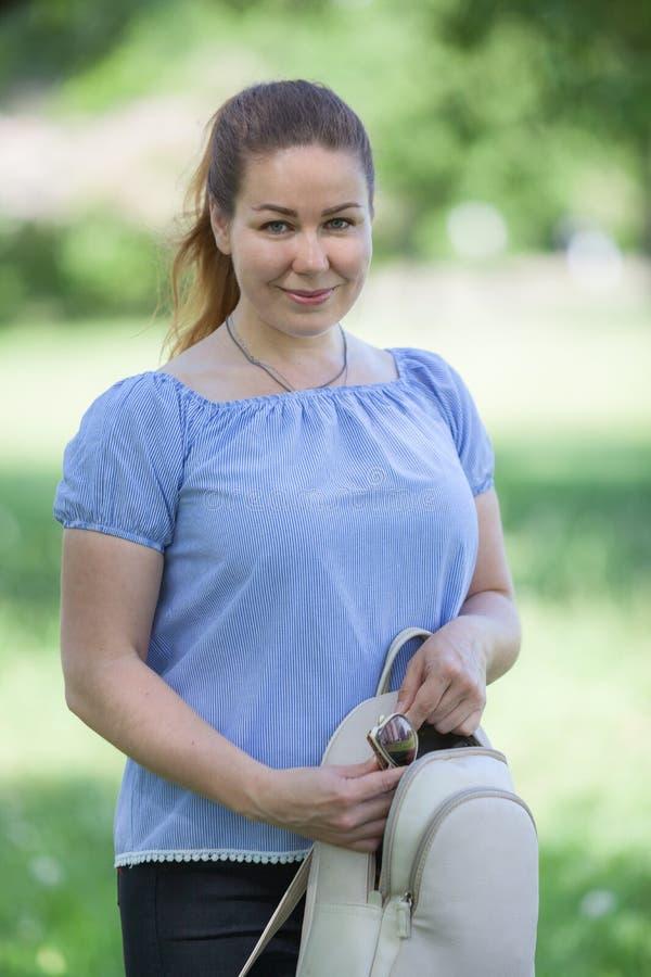 Портрет кавказской усмехаясь женщины с небольшим рюкзаком в парке лета стоковое изображение