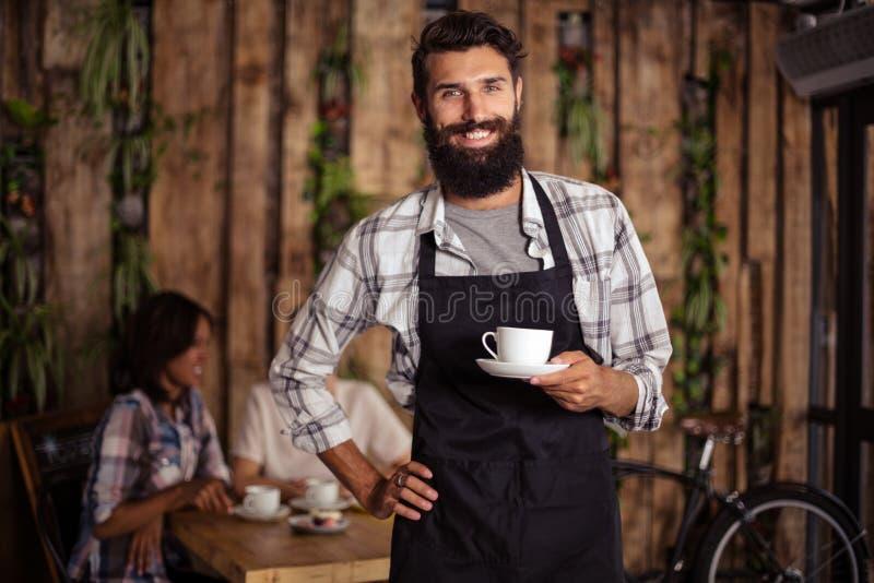 Портрет кельнера держа чашку кофе стоковые фото