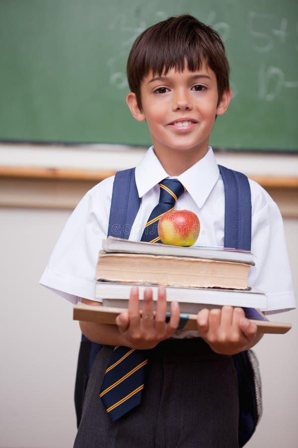 Портрет книг удерживания школьника и яблока стоковые изображения rf