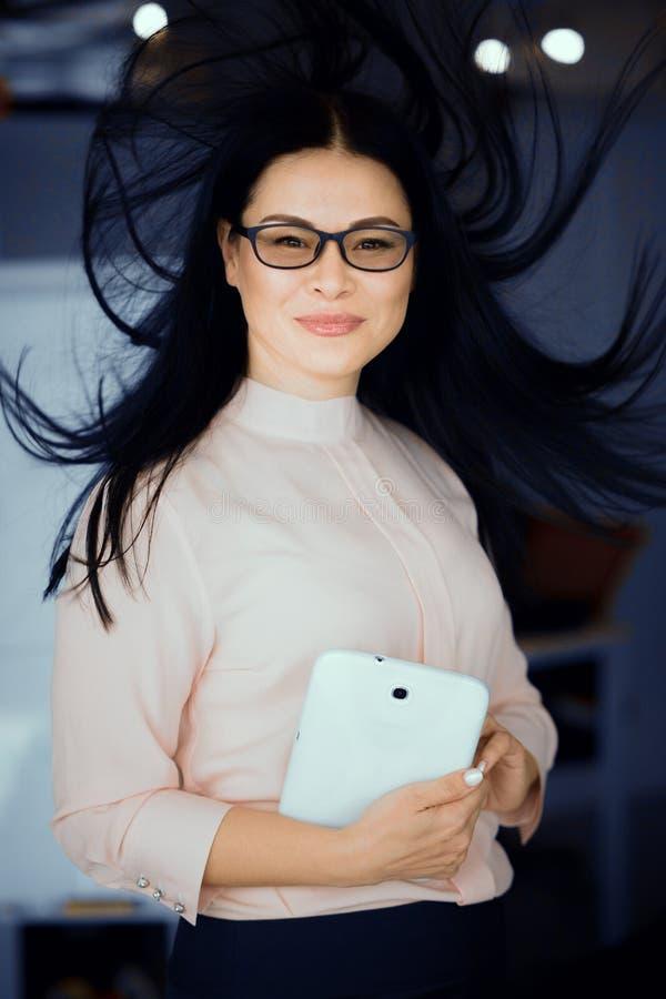 Портрет коммерсантки брюнет с ее волосами в воздухе стоковые изображения rf