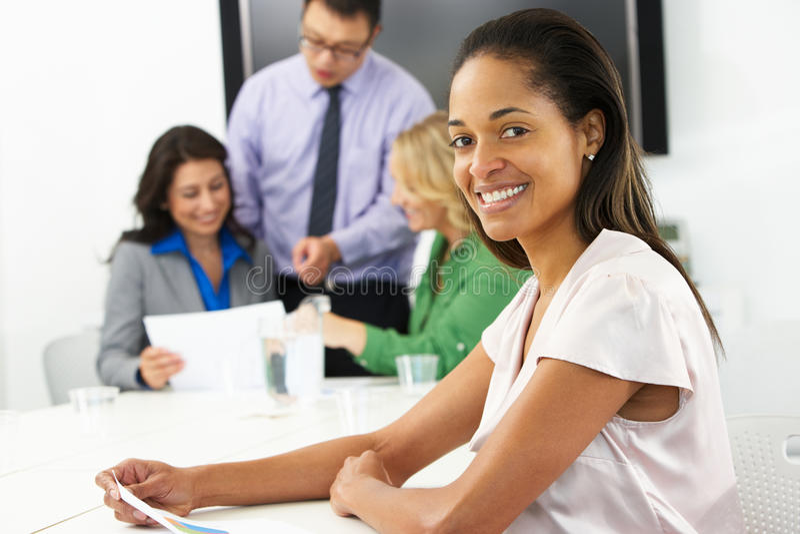 Портрет коммерсантки в зале заседаний правления с коллегами стоковое изображение rf