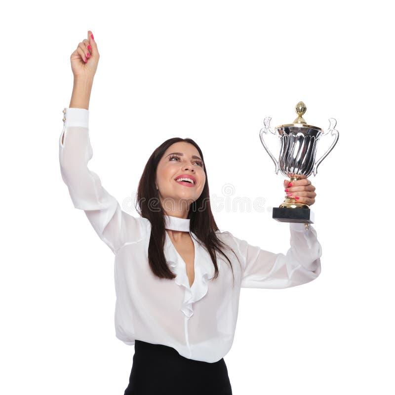Портрет коммерсантки держа трофей и празднуя пока l стоковое фото