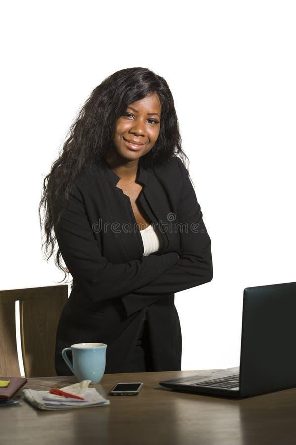Портрет компании офиса корпоративный молодой счастливой и привлекательной черной Афро-американской коммерсантки стоя на ее столе  стоковая фотография