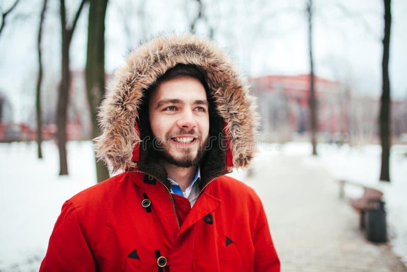 Портрет, конец-вверх человека детенышей стильно одетого усмехаясь с бородой одел в красной куртке зимы с клобуком и мехом на его стоковые фото