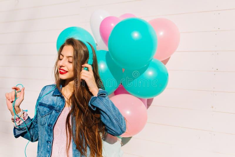 Портрет конца-вверх длинн-с волосами девушки брюнета в стильной куртке джинсовой ткани идя ко дню рождения Привлекательная молода стоковая фотография rf