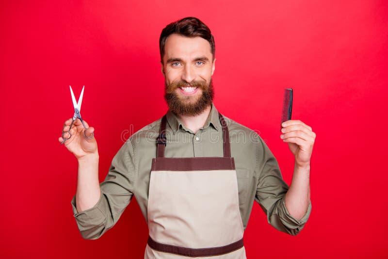 Портрет конца-вверх его он славное привлекательное жизнерадостное веселое бородатое удерживание владельца салона парня в аппарату стоковые изображения