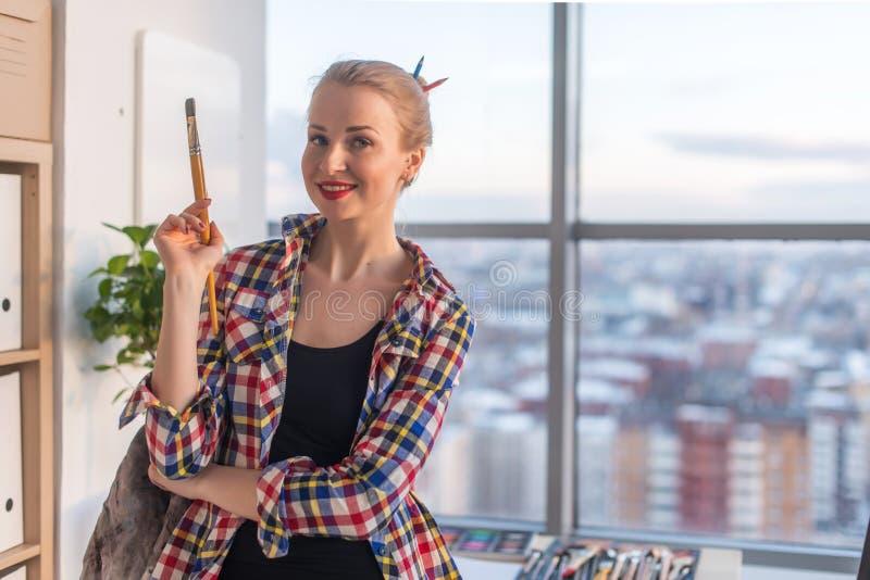 Портрет конца-вверх женского художника держа paintbrush, наблюдающ на камере, усмехаясь Новая творческого художника законченная стоковые фото