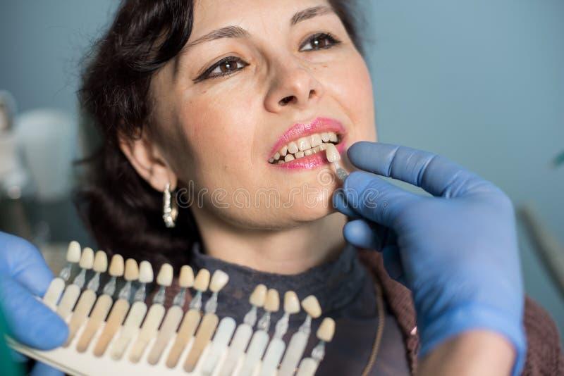 Портрет конца-вверх женщины в зубоврачебном офисе клиники Дантист проверяя и выбирая цвет зубов зубоврачевание стоковое фото