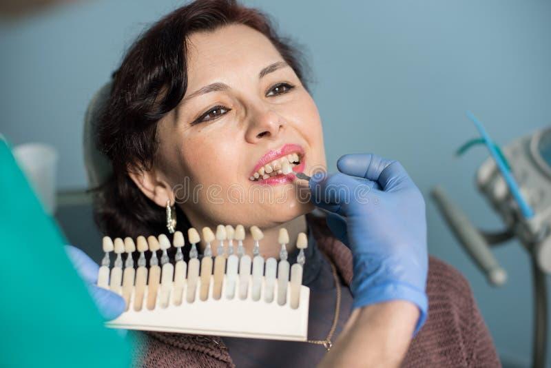Портрет конца-вверх женщины в зубоврачебном офисе клиники Дантист проверяя и выбирая цвет зубов стоковое фото rf