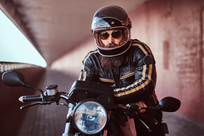 Портрет конца-вверх зверского бородатого велосипедиста в шлеме и солнечных очках одел в черной кожаной куртке сидя на a стоковое фото