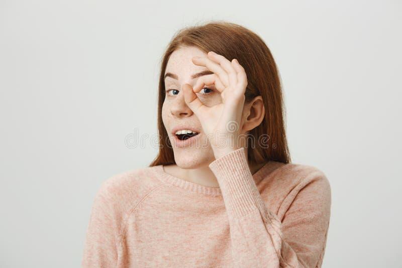 Портрет конца-вверх интересной прелестной европейской женщины redhead показывая знак monocle или телескопа и смотря до конца стоковое изображение rf