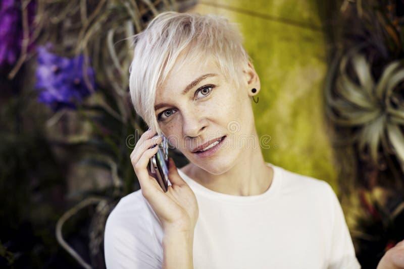 Портрет конца-вверх коротких волос красивой женщины битника белокурый мобильным телефоном Солнечный день в парке или саде стоковая фотография rf