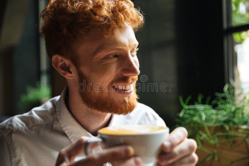 Портрет конца-вверх красивого усмехаясь человека readhead бородатого, владения стоковое фото