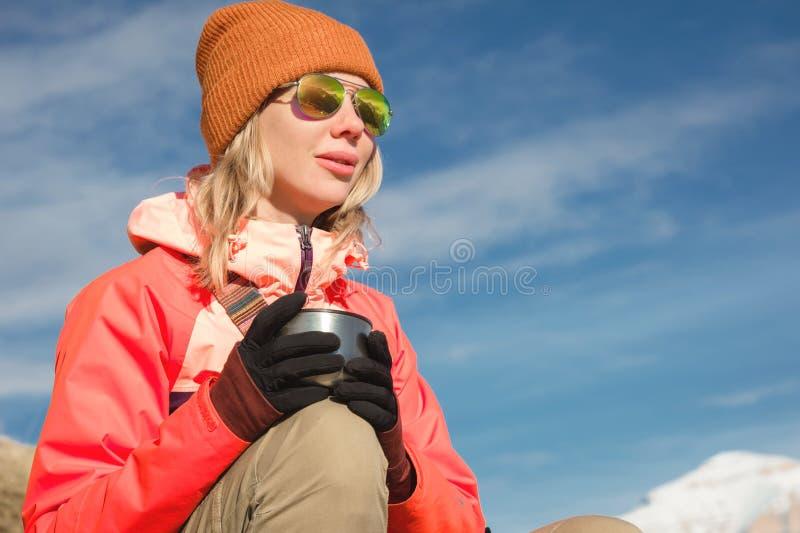 Портрет конца-вверх красивой девушки в шляпе и солнечных очках с кружкой кофе или чая пока сидящ на камне внутри стоковое изображение rf