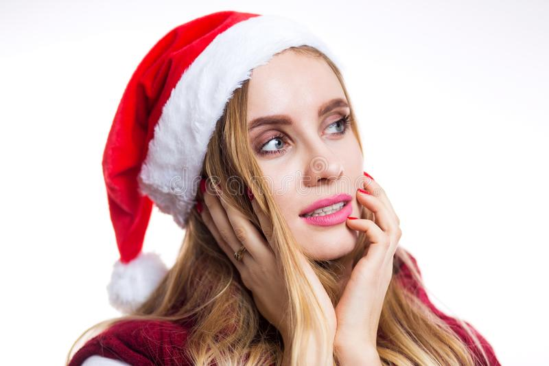 Портрет конца-вверх красивой женщины Санта в шляпе на белой предпосылке Девушка мечтает и думает около подарок на Новый Год стоковые фото