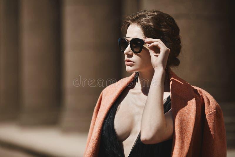 Портрет конца-вверх красивой, модной девушки брюнет в черном платье, пальто и солнечных очков, весны, outdoors стоковые фотографии rf