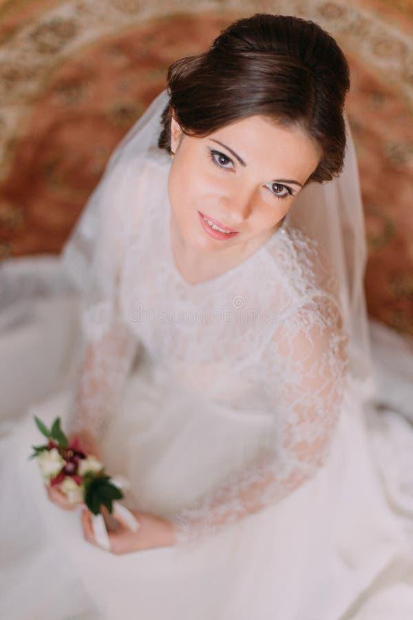 Портрет конца-вверх красивой усмехаясь невесты в платье свадьбы сидя на ковре и держа милый флористический boutonniere стоковые фото