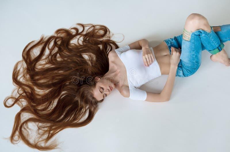 Портрет конца-вверх красоты красивой женской стороны при длинные коричневые волосы кладя вниз на белизну Концепция ухода за волос стоковое изображение