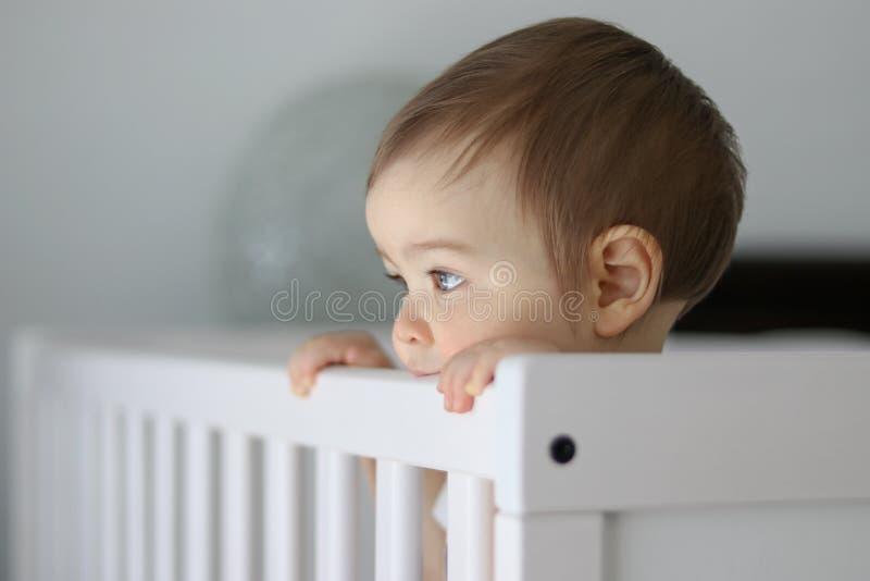 Портрет конца-вверх милого заботливого младенца оставаясь в его кроватке младенца держа сторону и daydreaming стоковое фото