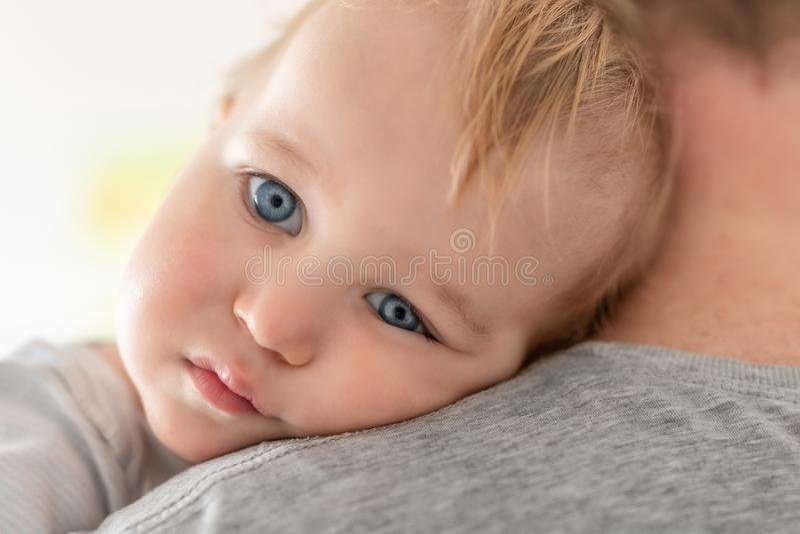 Портрет конца-вверх милого прелестного белокурого кавказского мальчика малыша на отцах взваливает на плечи внутри помещения Сладк стоковое фото rf