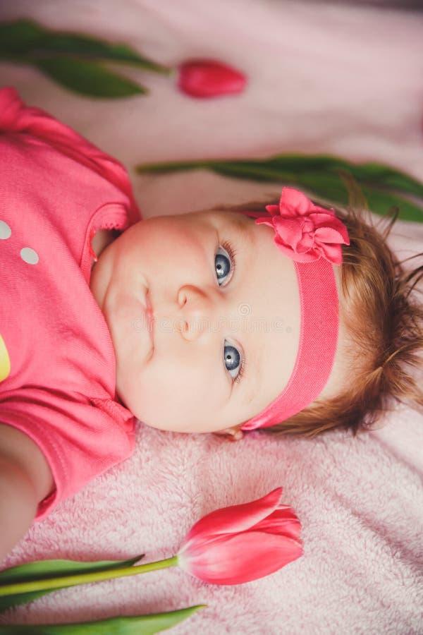 Портрет конца-вверх милого счастливого усмехаясь ребёнка лежа вниз на розовой кровати с тюльпанами вокруг стоковые изображения