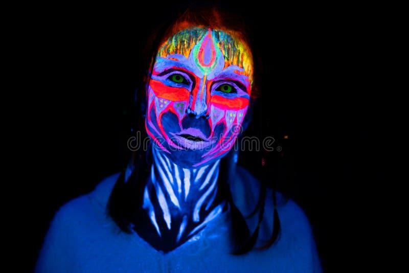 Портрет конца-вверх молодой нагой bodyarted женщины в голубой накаляя ультрафиолетов краске и желтых линзах окуляра Реальность во стоковые изображения rf