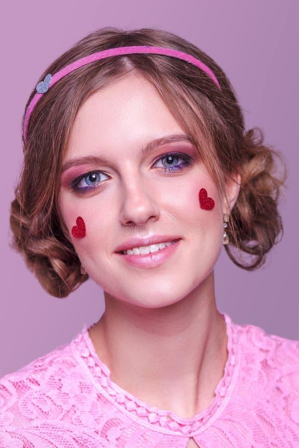 Портрет конца-вверх молодой положительной девушки с профессиональным ежедневным макияжем в розовых тенях с оправой и сердцах с яр стоковое изображение rf