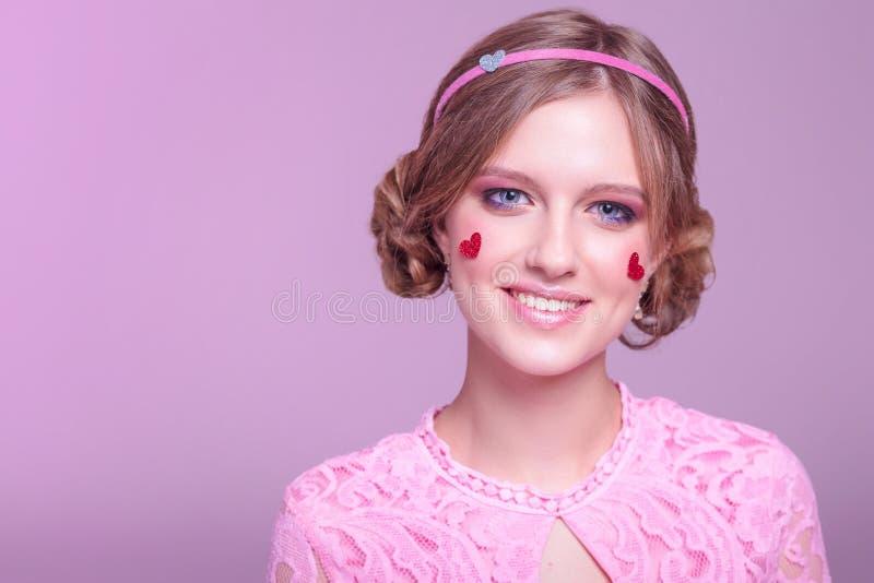 Портрет конца-вверх молодой положительной девушки с профессиональным ежедневным макияжем в розовых тенях с оправой и сердцах с яр стоковые фото