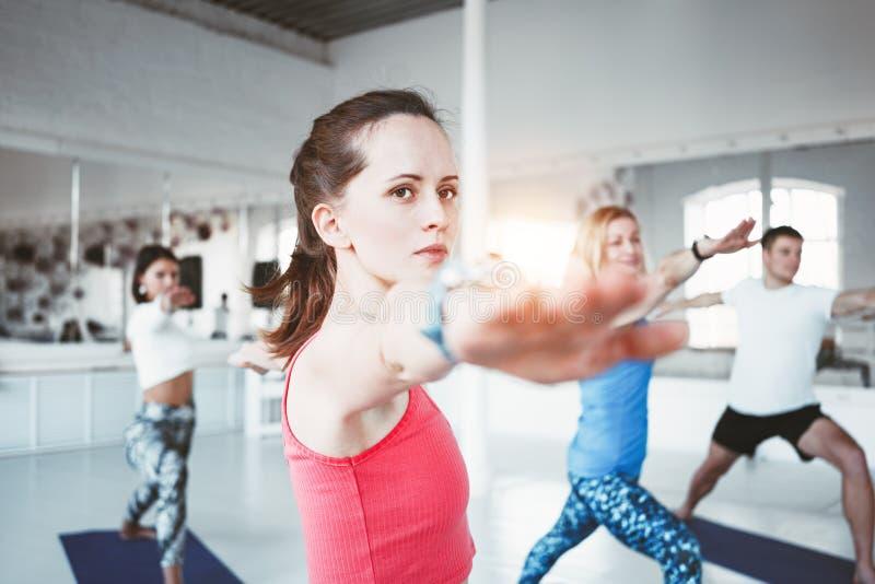 Портрет конца-вверх молодой sporty женщины делая йогу для того чтобы работать крытый класс вместе с ее друзьями запачканная предп стоковое фото rf