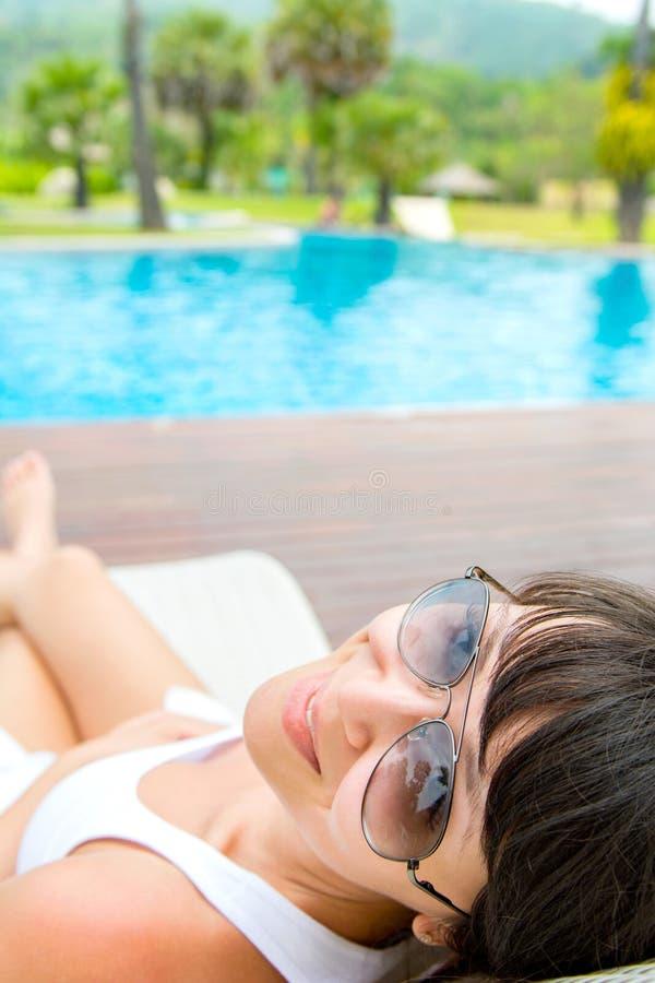Портрет конца-вверх молодой усмехаясь женщины с лежать солнечных очков стоковое фото