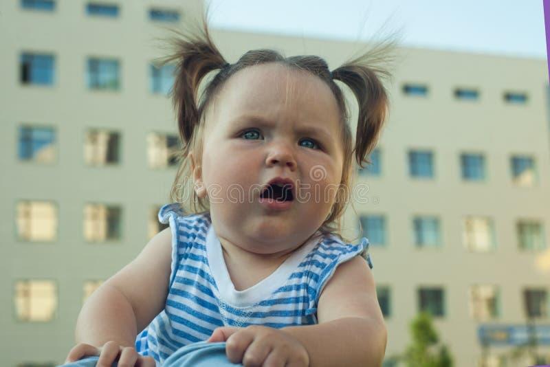 Портрет конца-вверх очень красивого ребёнка при светлые волосы и большие голубые глазы сидя на городской предпосылке ландшафта в  стоковые фотографии rf