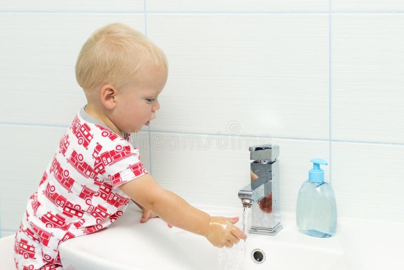 Портрет конца-вверх прелестное белое кавказское рук малыша одного мальчика годовалых моя в ванной комнате и смотреть удивленное e стоковая фотография rf