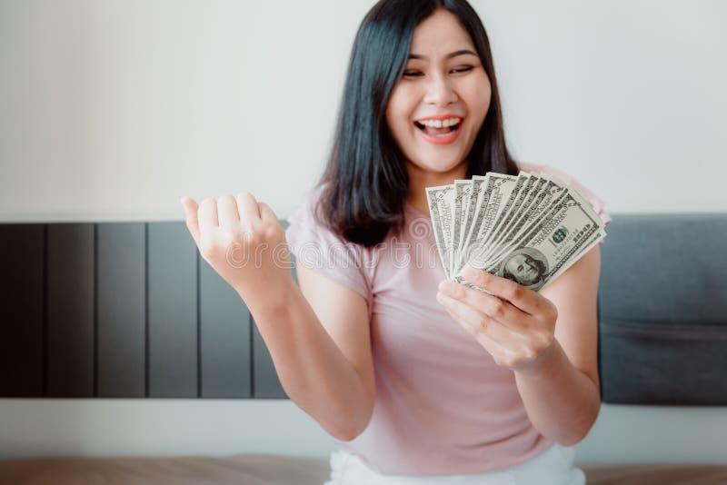 Портрет конца-Вверх привлекательной женщины держа наличные деньги денег от сбережений со счастливым выражением на ее спальне Дело стоковые фотографии rf